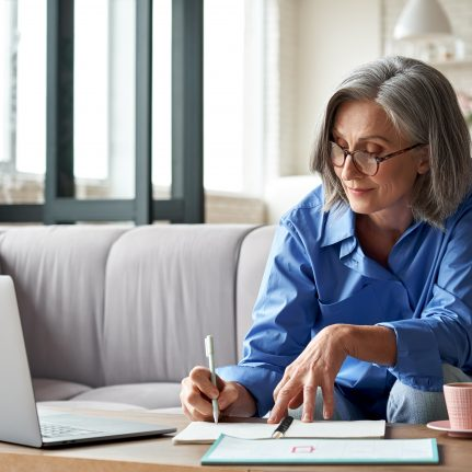 Woman watching webinar on laptop at home