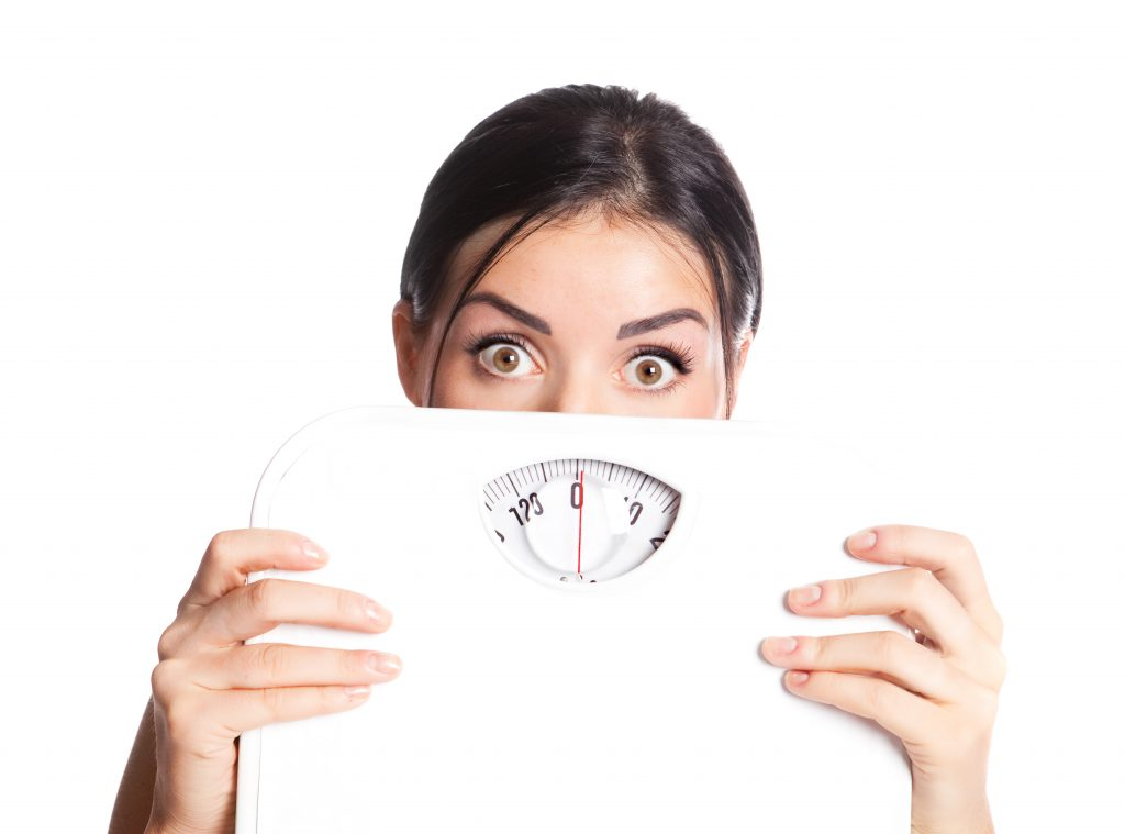 Woman holding scale looking scared